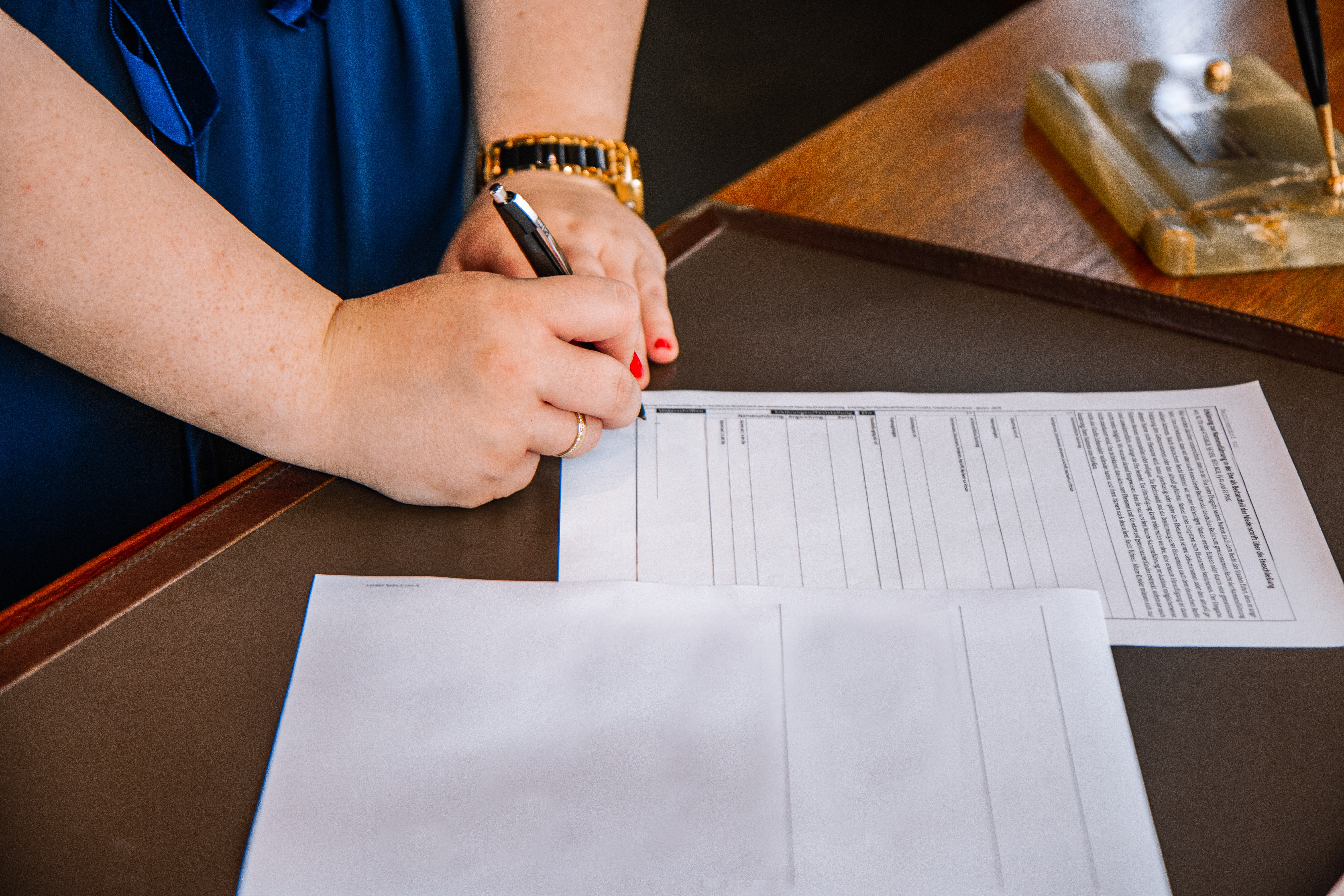 Woman at a notary signing a document